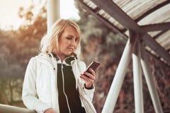 Blonde Frau auf der Brücke unter Verwendung des Smartphone Stockfotografie