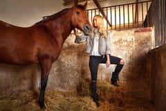 Blonde Frau auf einem Innenstall mit Pferd Stockfoto