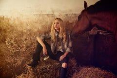 Blonde Frau auf einem Innenstall mit Pferd Lizenzfreie Stockbilder