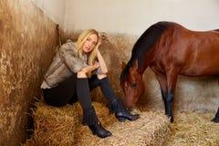 Blonde Frau auf einem Innenstall mit Pferd Lizenzfreies Stockbild
