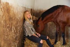 Blonde Frau auf einem Innenstall mit Pferd Lizenzfreie Stockfotografie