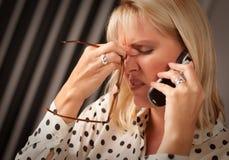 Blonde Frau auf Handy mit betontem Blick Stockfotografie