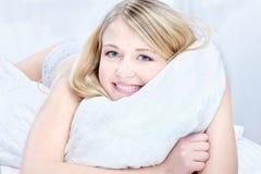 Blonde Frau auf Kissen Stockfotos