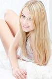 Blonde Frau auf Kissen im Schlafzimmer Stockbild