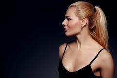 Blonde Frau auf schwarzem Hintergrund Lizenzfreie Stockfotografie