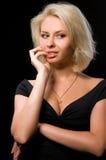 Blonde Frau auf schwarzem Hintergrund Stockfotografie
