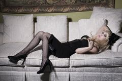 Blonde Frau auf Sofa Stockfotografie