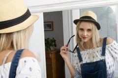 Blonde Frau Beautyful, die mit Sommerhut im Spiegel aufwirft Stockfotos