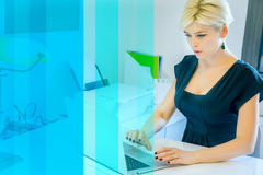 Blonde Frau bei der Arbeit im Büro Stockfotografie