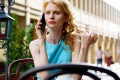 Blonde Frau bei Tisch im Pflasterungscafé, das auf Zelle spricht Stockfotografie