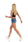 Blonde Frau beim Gehen der kurzen Jeanshose Lizenzfreie Stockbilder
