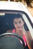 Blonde Frau betrachtet Ansicht durch Windfang des weißen Autos Lizenzfreies Stockfoto
