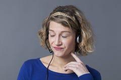 Blonde Frau bohrte tragende Kopfhörer mit den geschlossenen Augen Lizenzfreie Stockbilder