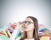 Blonde Frau in den Gläsern und in den Stapel von Büchern Stockbild