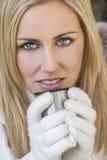 Blonde Frau in den Handschuhen warmes Getränk trinkend Stockfotos