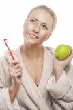 Blonde Frau in den Hausmantel-Reinigungs-Zähnen mit manuellem Toothbru Lizenzfreie Stockbilder