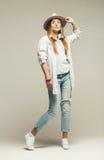 Blonde Frau in den Jeans und im Hut Stockfoto