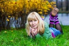Blonde Frau in den Manschetten, die auf dem Gras liegen Lizenzfreies Stockfoto