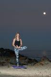 Blonde Frau in den Musterstrumpfhosen, die Balance und Flexibilität nachts durchführen Stockfotografie