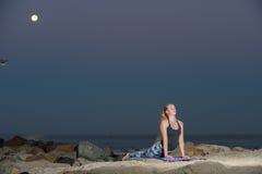 Blonde Frau in den Musterstrumpfhosen, die hintere Erweiterung nachts durchführen Stockfoto