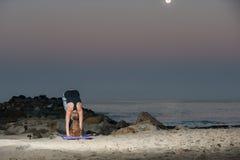 Blonde Frau in den Musterstrumpfhosen, die Kniesehne durchführen, dehnen nachts aus Lizenzfreie Stockbilder
