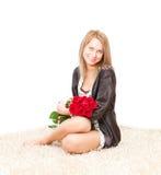 Blonde Frau in den Pyjamas mit roten Rosen Stockfoto
