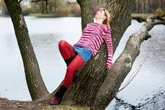 Blonde Frau in den roten Strümpfen, die auf dem Baum liegen Lizenzfreies Stockfoto
