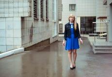 Blonde Frau in der blauen Kleider- und Denimjacke gehend hinunter die Stadtstraße gegen Hintergrund der städtischen Architektur Lizenzfreies Stockbild