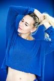 Blonde Frau in der blauen Strickjacke mit geschlossenen Augen Stockbild