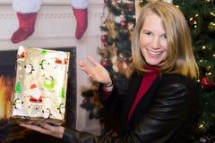 Blonde Frau in der Feiertags-Szene, die Geschenk hält Lizenzfreie Stockfotos