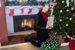 Blonde Frau in der Feiertags-Szene, die Geschenke nahe bei Baum hält Stockfotografie