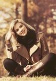 Blonde Frau der glücklichen jungen Mode, die auf dem Gras im Herbstwald sitzt Lizenzfreie Stockfotos