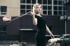 Blonde Frau der glücklichen jungen Mode im schwarzen Kleid gehend in Stadt s Stockbild