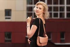 Blonde Frau der glücklichen jungen Mode im schwarzen Kleid gehend in Stadtstraße Lizenzfreies Stockbild