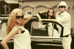 Blonde Frau der glücklichen jungen Mode im weißen Kleid nahe bei Weinleseauto Stockfotos