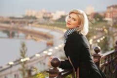 Blonde Frau der glücklichen Mode im schwarzen Mantel, der auf dem Zaun im Freien sich lehnt Stockfotografie