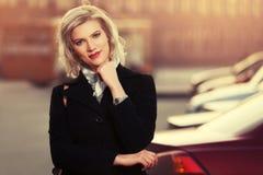 Blonde Frau der glücklichen Mode im schwarzen Mantel gehend in Stadtstraße Stockfotos