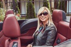 Blonde Frau der glücklichen Schönheit in der Sonnenbrille, die grünes Kleid und graue die Lederjacke sitzt auf einem Rücksitz in  Stockfotografie