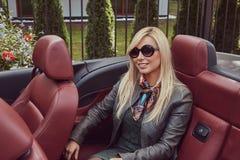 Blonde Frau der glücklichen Schönheit in der Sonnenbrille, die grünes Kleid und graue die Lederjacke sitzt auf einem Rücksitz in  Stockfoto