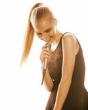 Blonde Frau der Junge die recht, die im Mikrofon singt, lokalisierte nah herauf Karaoke Stockfotografie