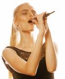 Blonde Frau der Junge die recht, die im Mikrofon singt, lokalisierte nah herauf Karaoke Stockbilder