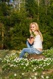 Blonde Frau der Junge recht auf einer Wiese mit Blumen Lizenzfreies Stockbild