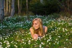 Blonde Frau der Junge recht auf einer Wiese mit Blumen Lizenzfreie Stockfotografie