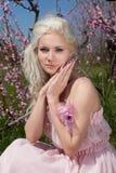 Blonde Frau der Junge recht in blühendem Garten Lizenzfreies Stockfoto