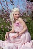 Blonde Frau der Junge recht in blühendem Garten Stockbild