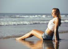 Blonde Frau der Junge recht an der gehenden Entspannung der Seeküste, Modedame bei Sonnenuntergang Stockbild