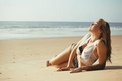 Blonde Frau der Junge recht an der gehenden Entspannung der Seeküste, Modedame bei Sonnenuntergang Lizenzfreies Stockbild