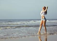 Blonde Frau der Junge recht an der gehenden Entspannung der Seeküste, Modedame bei Sonnenuntergang Stockfoto
