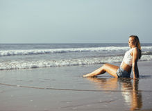 Blonde Frau der Junge recht an der gehenden Entspannung der Seeküste, Modedame bei Sonnenuntergang Lizenzfreie Stockfotografie