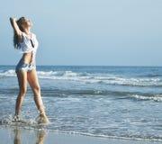 Blonde Frau der Junge recht an der gehenden Entspannung der Seeküste, Modedamensonnenuntergang, Leute auf Sommerferienkonzept Lizenzfreies Stockbild